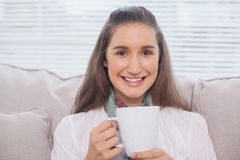 Smiling pretty model holding cup of coffee Royalty Free Stock Images
