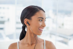 Smiling pretty model in sportswear listening to music Royalty Free Stock Photos