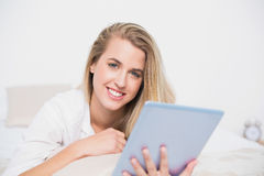 Smiling pretty model using her tablet pc lying on cosy bed Royalty Free Stock Photo