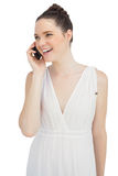 Smiling pretty model in white dress having phone call Stock Photography