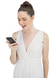 Smiling pretty model in white dress sending text message Royalty Free Stock Images