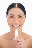 Smiling pretty natural model using chap stick Royalty Free Stock Images
