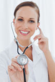 Smiling pretty nurse posing holding her stethoscope Royalty Free Stock Photography