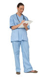 Smiling pretty nurse in scrubs writing on clipboard Royalty Free Stock Photo