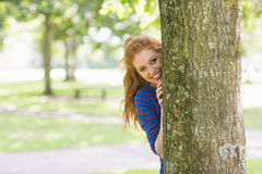 Smiling pretty redhead hiding behind a tree. On college campus Stock Photos