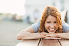 Smiling pretty redhead lying on bench on a sunny day Stock Photo