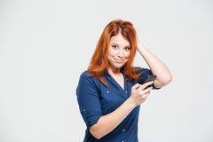 Smiling pretty redhead young woman using smartphone Stock Photo