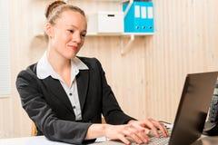 Smiling pretty secretary typing text on computer Stock Photos