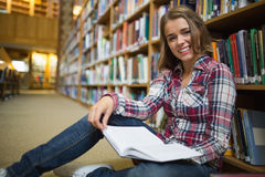 Smiling pretty student sitting on library floor reading book Royalty Free Stock Image