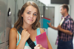 Smiling pretty student standing next to locker Stock Photography