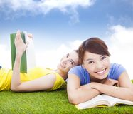 Smiling pretty students lying on the grassland with books Stock Photos