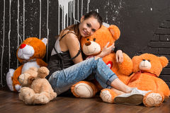 Smiling pretty stylish young woman hugs toys bear Royalty Free Stock Photos