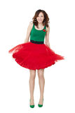 Smiling pretty teenage girl. Wearing old-fashioned dress isolated on white. Studio body portrait of shy young woman standing and holding red skirt royalty free stock photography