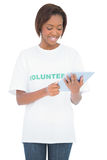 Smiling pretty volunteer looking at her tablet pc Royalty Free Stock Image