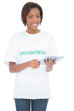 Smiling pretty volunteer using tablet pc Stock Images