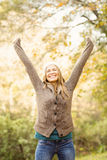 Smiling pretty woman with arms raised Stock Photography