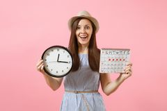 Smiling pretty woman in blue dress, hat holding round clock, periods calendar for checking menstruation days isolated on stock photos