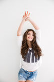 Smiling pretty woman in casual clothes standing with hands up Stock Photo