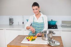 Smiling pretty woman chopping vegetables Royalty Free Stock Photography