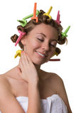 Smiling pretty woman with closed eyes and curlers on hair. Stock Photo