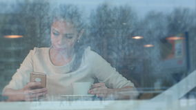 Smiling pretty woman with a cup of tea texting on smartphone in a cafe. Viewed through the window. Professional shot on BMCC RAW with high dynamic range. You stock video footage