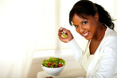 Smiling pretty woman eating green salad Royalty Free Stock Images