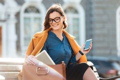 Smiling pretty woman in eyeglasses and coat holding mobile phone royalty free stock photography