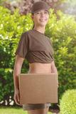 Smiling Pretty Woman at the Garden Holding a Box. Portrait of a Smiling Pretty Woman at the Garden Holding a Cardboard Box and Looking at the Camera royalty free stock image