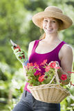 Smiling pretty woman gardener. Smiling young woman cutting flowers in her garden Royalty Free Stock Photos