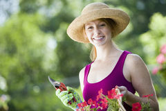 Smiling pretty woman gardener. Smiling young woman cutting flowers in her garden Royalty Free Stock Photo