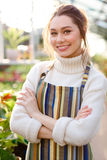 Smiling pretty woman gardener standing with arms crossed in greenhouse Royalty Free Stock Image