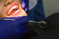 Smiling pretty woman is having her teeth examined by the dentist in clinic. royalty free stock photos