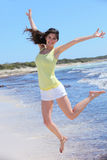Smiling Pretty Woman in Jump Shot at Beach Stock Photography