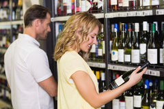 Smiling pretty woman looking at wine bottle Stock Photo