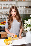 Smiling pretty woman making orange juice Stock Photography