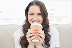 Smiling pretty woman in pyjamas having coffee Stock Image