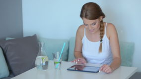 Smiling pretty woman reading her tablet screen Stock Images