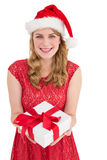Smiling pretty woman in red dress offering present Royalty Free Stock Photography