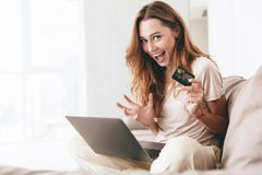 Smiling pretty woman showing credit card to camera. While working with laptop on sofa Royalty Free Stock Photography