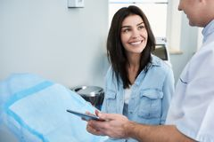 Smiling pretty woman is talking with surgeon stock image