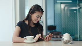 Smiling pretty woman texting on smartphone in a cafe. Professional shot on BMCC RAW with high dynamic range. You can use it e.g. in your commercial video stock video footage