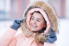 Smiling happy pretty woman in warm winter jacket outdoors enjoys winter journey, weared gloves and hood, a lot of snow. Smiling pretty woman in warm winter Royalty Free Stock Images