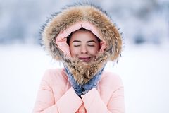 Smiling happy pretty woman in warm winter jacket outdoors enjoys winter journey, weared gloves and hood, a lot of snow. Smiling pretty woman in warm winter Royalty Free Stock Photo