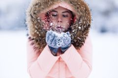 Smiling happy pretty woman in warm winter jacket outdoors enjoys winter journey, weared gloves and hood, a lot of snow royalty free stock image