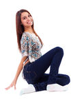 Smiling pretty woman wearing jeans sitting on a floor Stock Photos
