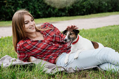Smiling pretty 20-25 years girl with foxterrier. Smiling pretty 20-25 years girl in tartan red shirt with long hair lies on the grass with her active foxterrier stock images