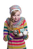 Smiling pretty young girl wearing coloful knitted scarf, hat and mittens, holding christmas gift isolated. Stock Photography