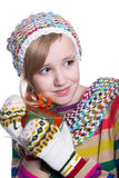 Smiling pretty young girl wearing coloful knitted scarf, hat and mittens, holding christmas gift isolated on white background. Royalty Free Stock Photography