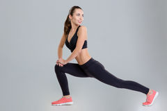 Smiling pretty young sportswoman stretching her legs and looking back Stock Images