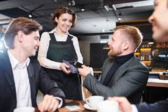 Pretty waitress giving terminal for payment to businessman stock image